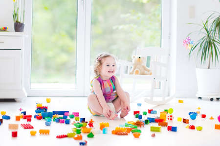messy house: Sweet laughing toddler girl playing with colorful blocks sitting on a floor in a sunny bedroom with a big window