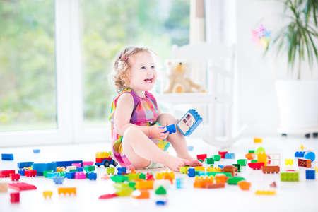 Schattige lachende peuter meisje spelen met kleurrijke blokken zitten op een vloer in een zonnige slaapkamer met een groot raam