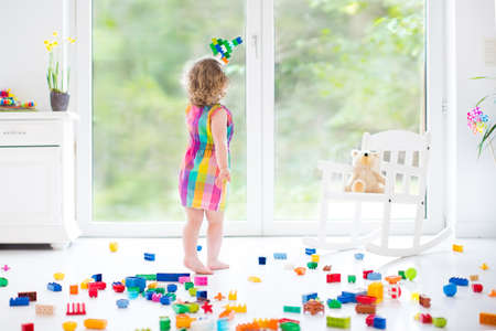 Cute laughing toddler girl playing with colorful blocks, building and airplane in a sunny bedroom with a big window