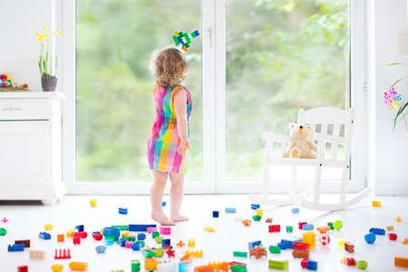 Cute lachende peuter meisje spelen met kleurrijke blokken, gebouw en vliegtuig in een zonnige slaapkamer met een groot raam