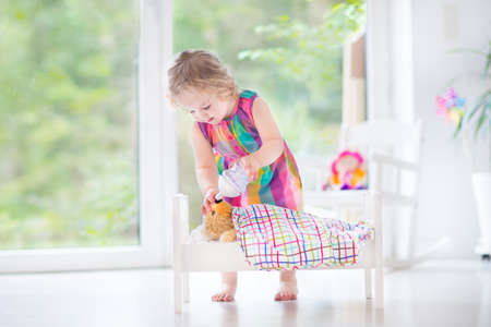 Cute curly toddler girl feeding her toy bear in a white crib playing in a sunny bedroom with big garden view windows   photo