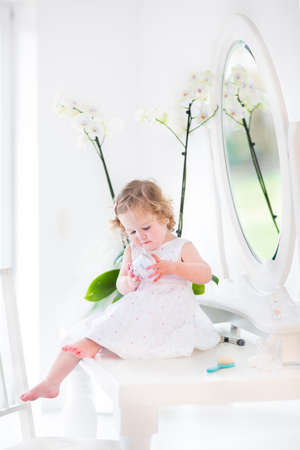 hair dresser: Beautiful toddler girl playing with cosmetics sitting on her mother s white dresser with a round mirror on a sunny morning