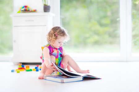 Drôle bouclés bébé fille lisant un livre assis sur le sol dans une chambre blanche ensoleillée avec de grandes fenêtres avec vue sur le jardin avec des jouets autour d'elle