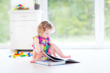 Funny curly toddler girl reading a book sitting on the floor in a sunny white bedroom with big garden view windows with toys around her