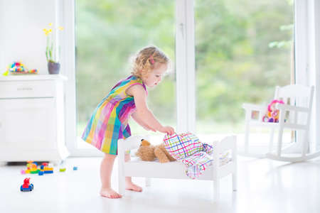 Sweet toddler girl playing with her teddy bear in a sunny room with big garden view windows   photo