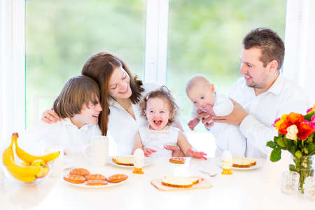 Happy young family with a teenage boy, adorable curly toddler girl and a newborn baby having fun together on a Sunday morning having breakfast in a white dining room with a big window   Stock Photo