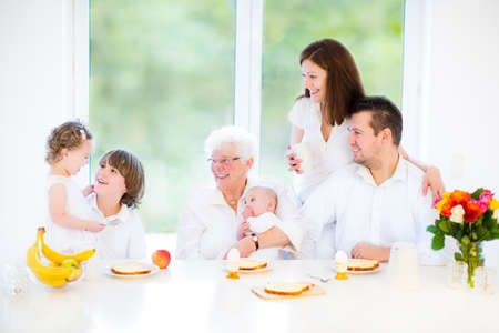 big family: Happy young family with a teenage boy, adorable curly toddler girl and a newborn baby having fun together on a Sunday morning having breakfast in a white dining room with a big window   Stock Photo