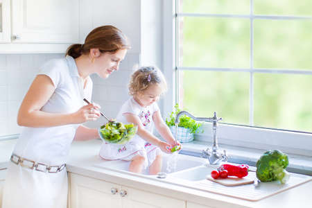Young mother and her cute toddler daughter cooking together a healthy salad for lunch in a beautiful white sunny kitchen with a big window