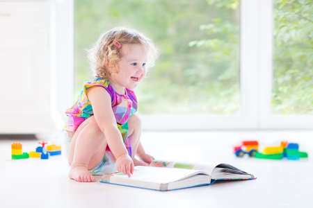 Funny curly toddler girl reading a book sitting on the floor in a sunny bedroom with big garden view windows with toys around her