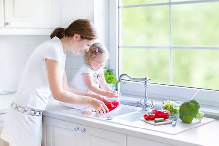 dishes: Young mother and her funny curly toddler daughter washing vegetables together in a kitchen sink getting ready to make salad for lunch in a sunny white kitchen with a big garden view window
