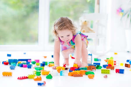 Beautiful toddler girl with curly hair sitting on a floor in a toy mess in a sunny white bedroom with big windows with garden view playing with colorful construction blocks