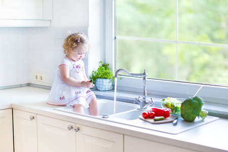 Cute funny toddler girl washing vegetables in a kitchen sink helping her mother to cook salad for lunch in a beautiful white kitchen with a big window with garden view   Banque d'images