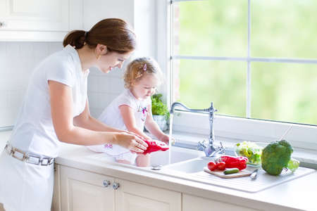 Young beautiful mother and her cute curly toddler daughter washing vegetables together in a kitchen sink getting ready to cook salad for lunch in a sunny white kitchen with a big garden view window   Banque d'images