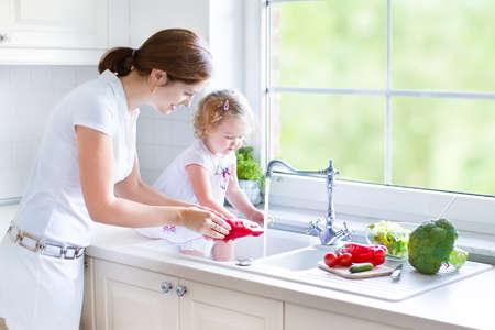 Jonge mooie moeder en haar schattige krullend peuter dochter wassen van groenten samen in een gootsteen klaar om salade voor de lunch koken in een zonnige witte keuken met een grote tuin venster Stockfoto