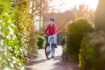 Happy smiling teenager boy riding his bike on sunset   photo