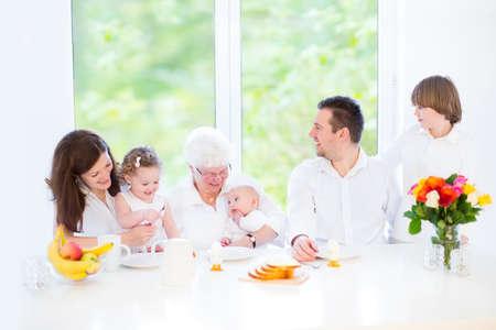 Familia joven feliz con tres hijos - muchacho adolescente, muchacha del niño y del bebé recién nacido - divirtiéndose juntos durante un desayuno de Pascua visitando a su abuela, en un comedor blanco con ventana grande Foto de archivo