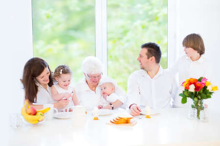 Happy young family with three children - teenager boy, toddler girl and newborn baby - having fun together during an Easter breakfast visiting their grandmother, in a white dining room with big window   Stock Photo