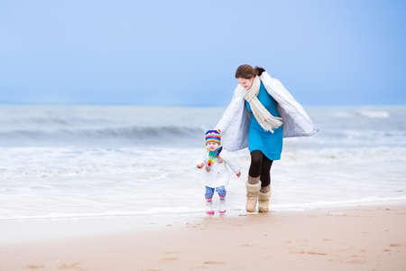 Young active mother and her cute toddler daughter running together on a beautiful windy winter beach in Holland   photo