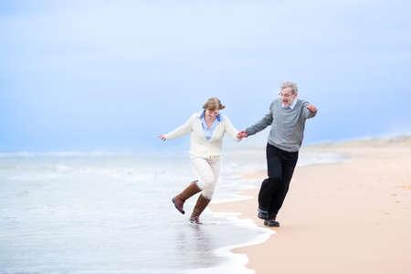 vejez feliz: Feliz pareja de mediana edad que se ejecuta en una playa de la mano y saltando lejos de las olas