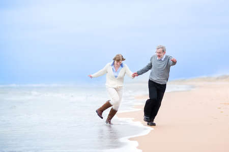 retirement age: Happy middle aged couple running on a beach holding hands and jumping away from the waves