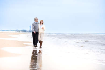retirement age: Happy loving middle aged couple walking on a beautiful beach in Holland   Stock Photo