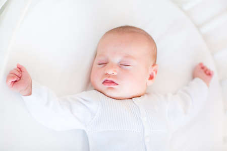 Little newborn baby boy sleeping in a white round crib   photo