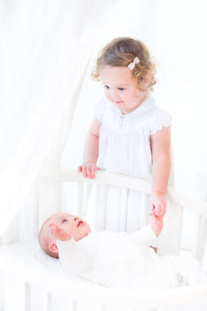 Adorable siblings, newborn baby boy and a toddler girl, holding hands and playing in a white sunny bedroom with a round crib   photo
