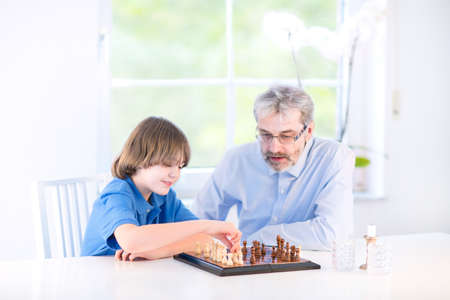 Cute happy boy playing chess with his grandfather sitting at a window in a white living room   photo