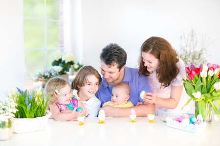 Happy young family with three children - teenager boy, cute toddler girl and a newborn baby - enjoying Easter breakfast in a white sunny dining room with a big garden view window   Stock Photo