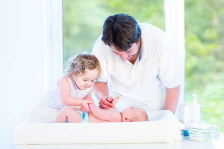 Cute newborn baby looking at his father and toddler sister changing his diaper in a room with a big window   photo