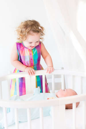 Cute newborn baby boy looking at his toddler sister standing at his white round crib on a sunny morning   photo
