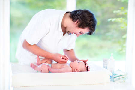 Young loving father changing diaper of his newborn baby son, holding lotion bottle in his hand, standing in a sunny bedroom with a big garden view window   photo