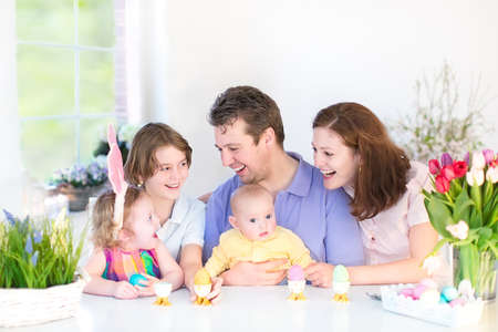 Happy young family with three children - teenager boy, cute toddler girl and a newborn baby - enjoying breakfast in a white sunny dining room with a big garden view window