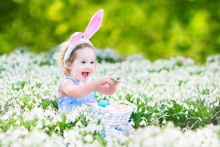 niños pintando: Muchacha adorable del niño con orejas de conejo jugando con los huevos de Pascua en una cesta blanca sentado en un jardín soleado, con las primeras flores de primavera en blanco