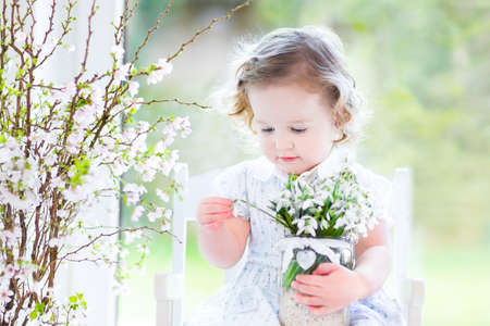 Beautiful curly toddler girl in a white dress sitting in a white rocking chair next to a big garden view window holding first spring flowers in a transparent crystal vase