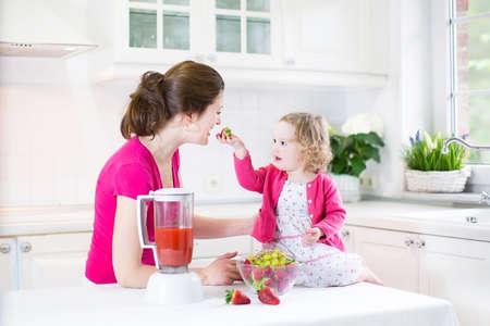 licuadora: Feliz riendo muchacha del niño y su hermosa madre joven que hace la fresa fresca y otra de jugo de fruta para el desayuno juntos en una cocina blanca soleado con una ventana Foto de archivo