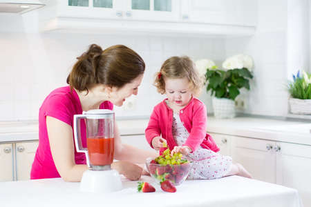little girl eating: Happy laughing toddler girl and her beautiful young mother making fresh strawberry and other fruit juice for breakfast together in a sunny white kitchen with a window
