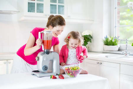 kitchen appliances: Happy laughing toddler girl and her beautiful young mother making fresh strawberry and other fruit juice for breakfast together in a sunny white kitchen with a window