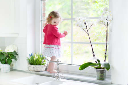 Cute toddler girl in a red dress watching out a window in a beautiful white sunny kitchen with spring flowers   Stockfoto