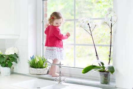 Schattige peuter meisje in een rode jurk te kijken uit het raam in een mooie witte zonnige keuken met lentebloemen