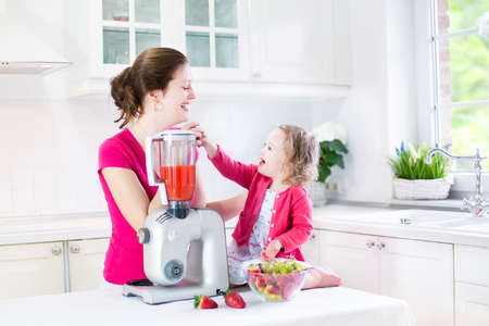 kitchen device: Happy laughing toddler girl and her beautiful young mother making fresh strawberry and other fruit juice for breakfast together in a sunny white kitchen with a window
