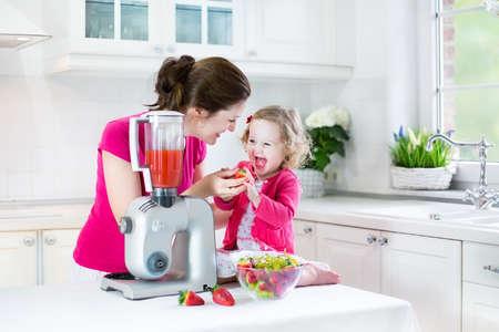 niños cocinando: Feliz riendo muchacha del niño y su hermosa madre joven que hace la fresa fresca y otra de jugo de fruta para el desayuno juntos en una cocina blanca soleado con una ventana Foto de archivo