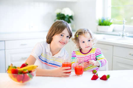 Happy teenager boy and his cute toddler sister having fruit for breakfast before school and kindergarten drinking juice in a sunny white kitchen with a window   photo