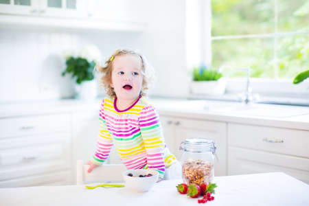 playing with spoon: Beautiful toddler girl with curly hair wearing a colorful shirt having breakfast drinking juice in a white sunny kitchen with a garden view window