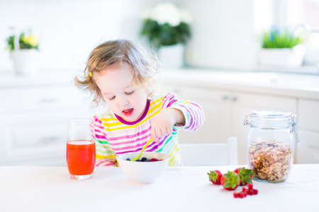 eating banana: Beautiful toddler girl with curly hair wearing a colorful shirt having breakfast drinking juice in a white sunny kitchen