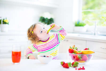 eating breakfast: Beautiful toddler girl with curly hair wearing a colorful shirt having breakfast drinking juice and eating corn flakes with strawberry in a white sunny kitchen with a garden view window   Stock Photo