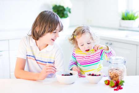 niños desayunando: Muchacho adolescente feliz y su hermana niño lindo tener fruta y cereal con fresas para el desayuno antes de la escuela y jardín de infantes, beber jugo en una cocina blanca soleado con una ventana