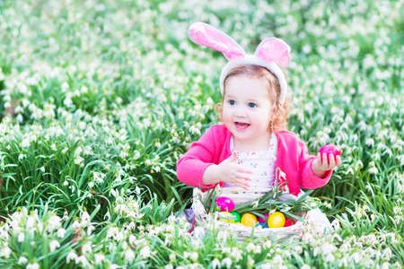 bunny ears: Adorable toddler girl wearing bunny ears playing with Easter eggs in a white basket sitting in a sunny garden with first white spring flowers   Stock Photo