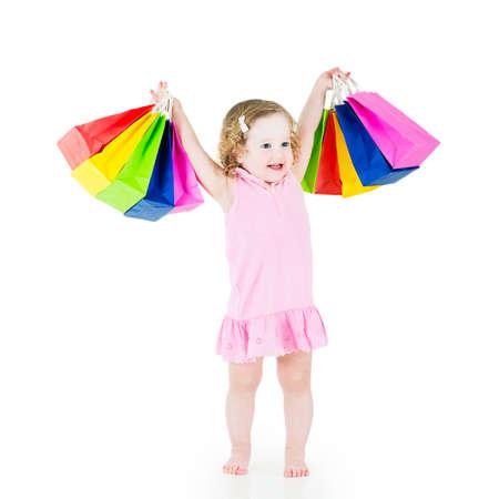 petite fille avec robe: Adorable petite fille aux cheveux boucl�s portant une robe rose est heureux apr�s la vente et achats sp�cial montrant ses sacs color�s Banque d'images