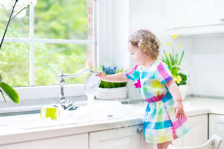 dish washing: Cute curly toddler girl in a colorful dress washing dishes, cleaning with a sponge and playing with foam in the sink in a beautiful sunny white kitchen with a garden view window in a modern home